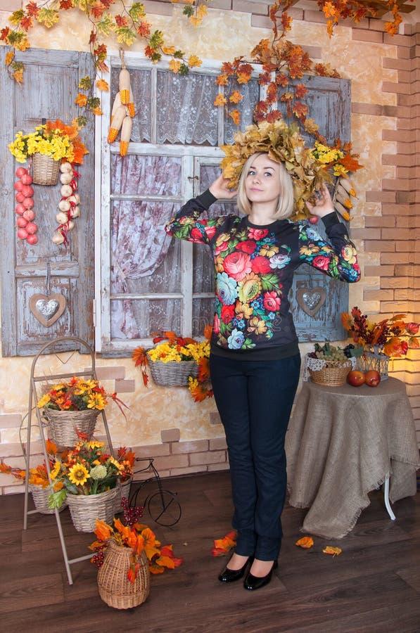 Όμορφη γυναίκα με το στεφάνι των φύλλων φθινοπώρου Νέο standi γυναικών στοκ φωτογραφία