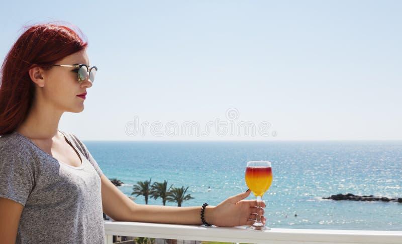Όμορφη γυναίκα με το χυμό φρούτων στο γυαλί υπό εξέταση στο υπόβαθρο θάλασσας στοκ εικόνες