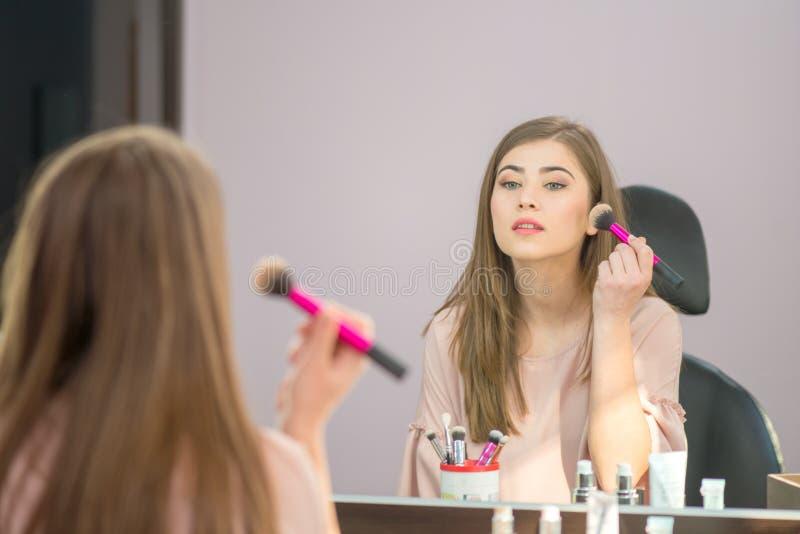 Όμορφη γυναίκα με το hairstyle και makeup εξέταση τον καθρέφτη στο σαλόνι ομορφιάς στοκ εικόνες