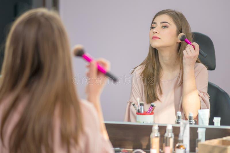 Όμορφη γυναίκα με το hairstyle και makeup εξέταση τον καθρέφτη στο σαλόνι ομορφιάς στοκ εικόνα με δικαίωμα ελεύθερης χρήσης