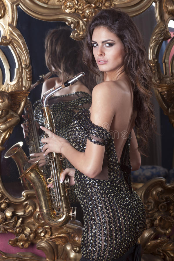 Όμορφη γυναίκα με το saxophone στοκ εικόνα