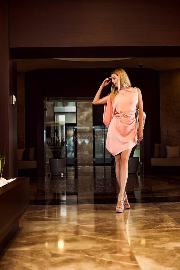 Όμορφη γυναίκα μόδας στο ασυμμετρικό ρόδινο φόρεμα στοκ εικόνες