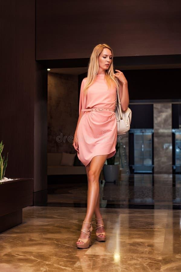 Όμορφη γυναίκα μόδας στο ασυμμετρικό ρόδινο φόρεμα στοκ εικόνα