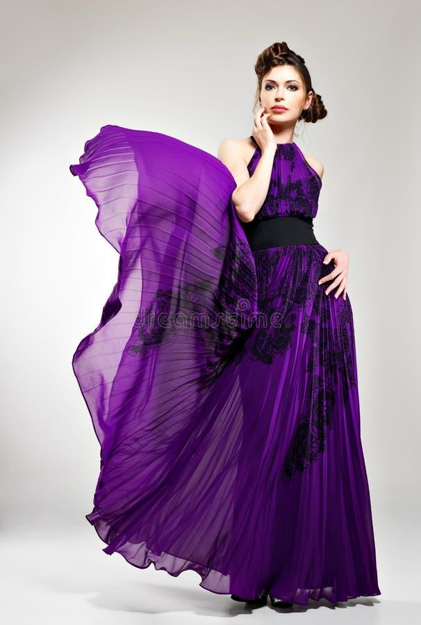 Όμορφη γυναίκα μόδας στο ιώδες μακρύ φόρεμα στοκ εικόνες