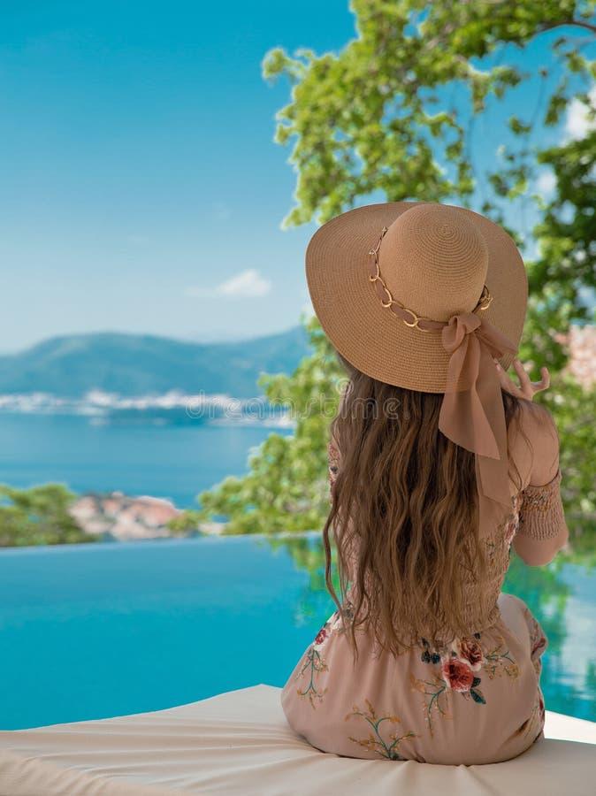 Όμορφη γυναίκα μόδας στο καπέλο παραλιών που απολαμβάνεται τη θέα θάλασσας από το swimmi στοκ εικόνες