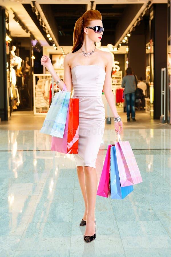 Όμορφη γυναίκα μόδας με τις τσάντες αγορών στοκ φωτογραφία
