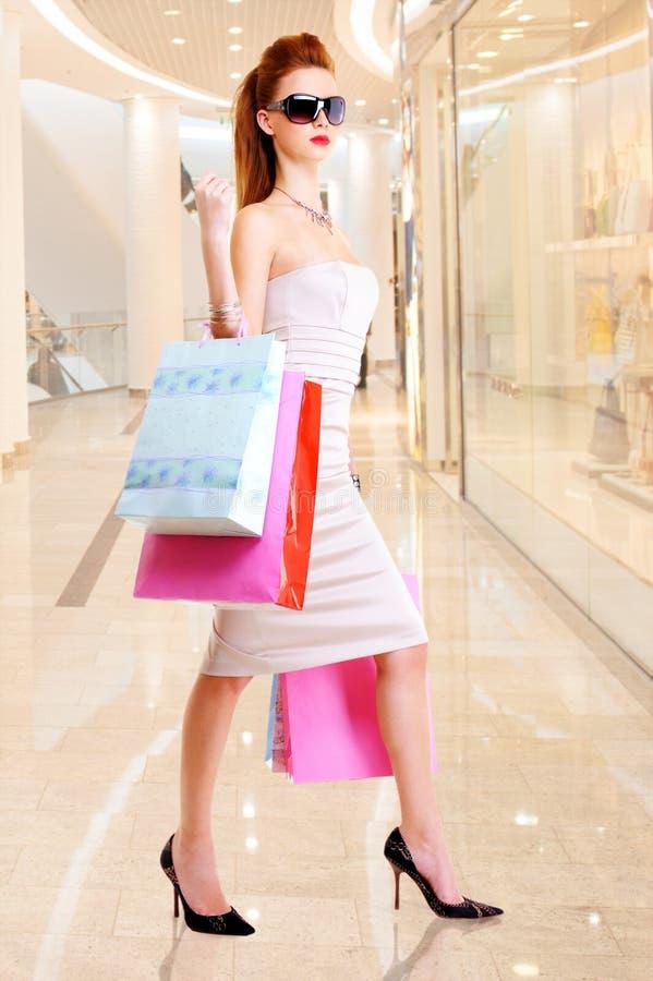 Όμορφη γυναίκα μόδας με τις τσάντες αγορών στοκ εικόνα με δικαίωμα ελεύθερης χρήσης
