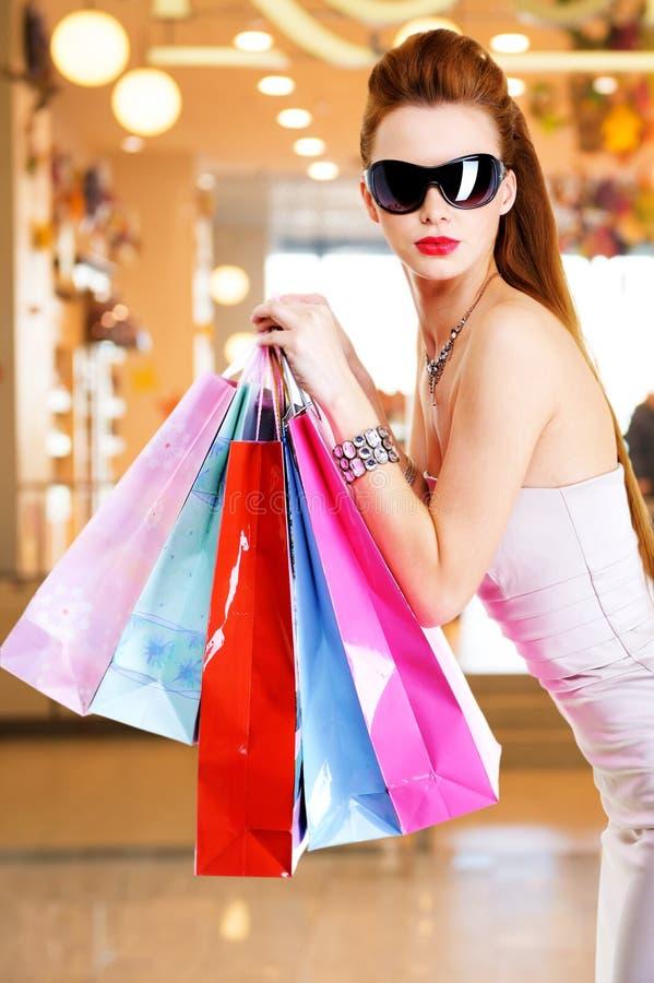 Όμορφη γυναίκα μόδας με τις τσάντες αγορών στοκ εικόνες