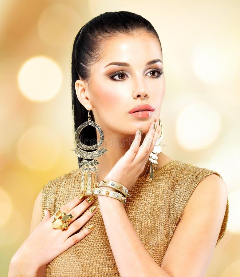 Όμορφη γυναίκα μόδας με το μαύρο makeup και το χρυσό μανικιούρ στοκ φωτογραφία