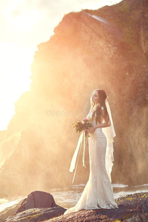 Όμορφη γυναίκα νυφών που στέκεται στους βράχους θαλασσίως Νύφη στο ηλιοβασίλεμα στοκ φωτογραφίες
