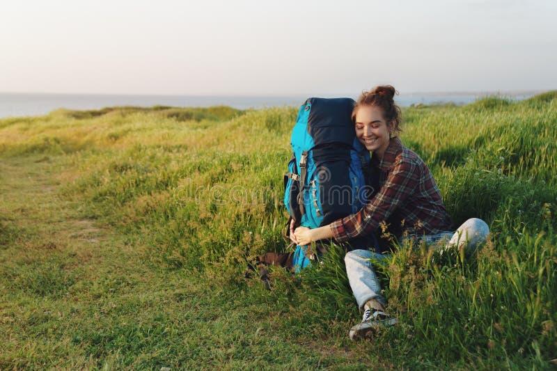 Όμορφη γυναίκα οδοιπόρων που αγκαλιάζει το σακίδιο πλάτης της στη χλόη και το χαμόγελο στοκ εικόνες