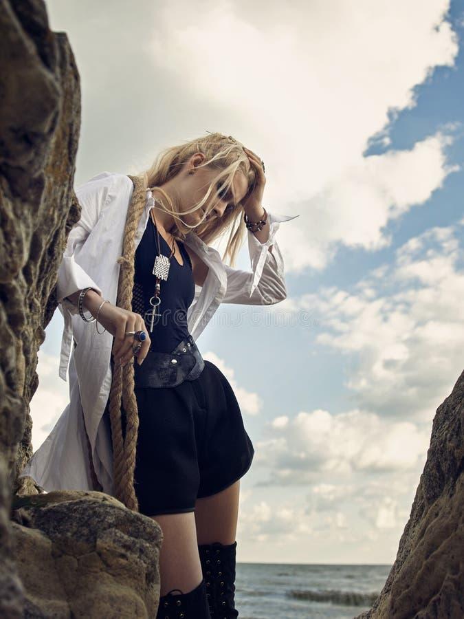 Όμορφη γυναίκα πειρατών που στέκεται στην παραλία στις μπότες στοκ φωτογραφίες