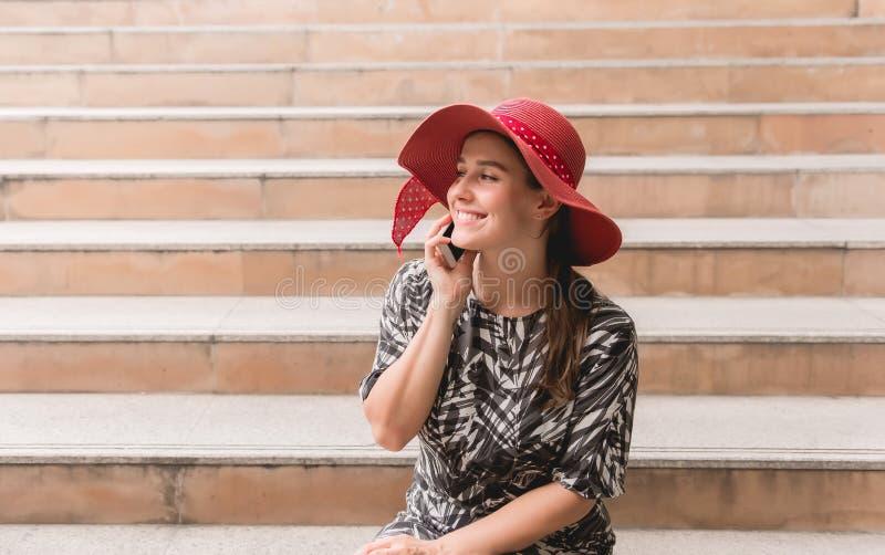 Όμορφη γυναίκα πορτρέτου χρησιμοποιώντας το smartphone και sittiing στο σκαλοπάτι, ευτυχής και χαμογελώντας στοκ εικόνα με δικαίωμα ελεύθερης χρήσης