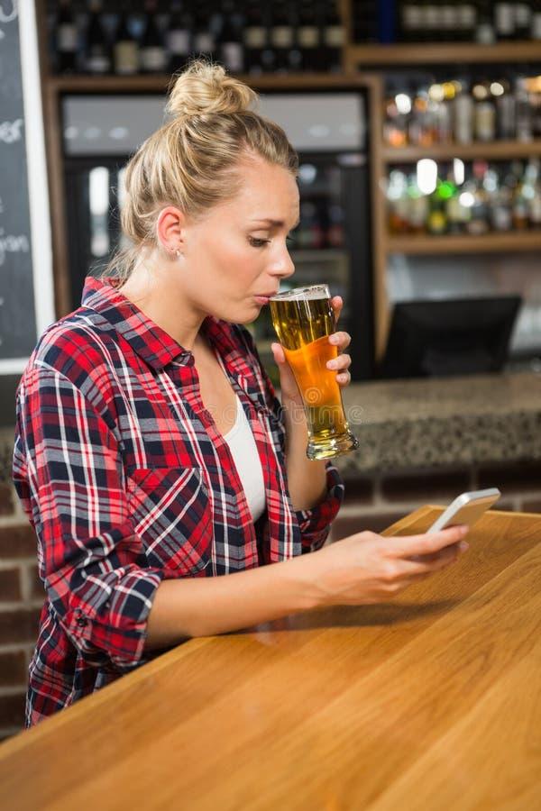 Όμορφη γυναίκα που έχει μια μπύρα και που εξετάζει το smartphone στοκ φωτογραφίες