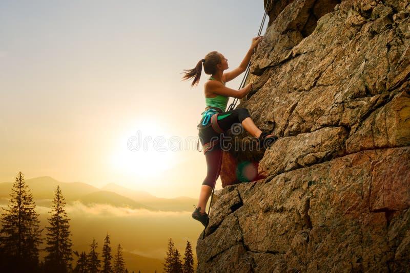 Όμορφη γυναίκα που αναρριχείται στο βράχο στο ομιχλώδες ηλιοβασίλεμα στα βουνά Περιπέτεια και ακραία αθλητική έννοια στοκ φωτογραφίες