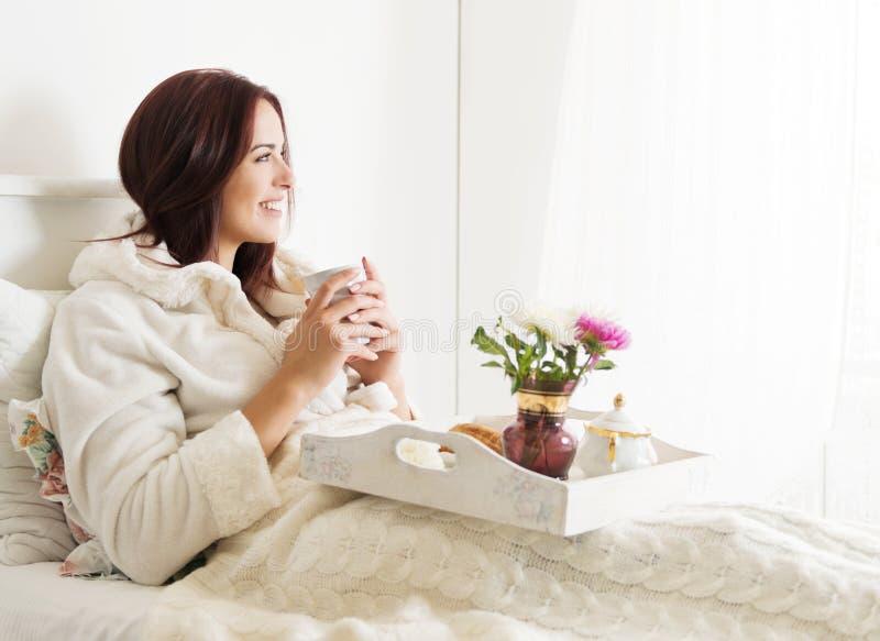 Όμορφη γυναίκα που βάζει και που απολαμβάνει το πρόγευμα στο κρεβάτι στοκ εικόνες με δικαίωμα ελεύθερης χρήσης