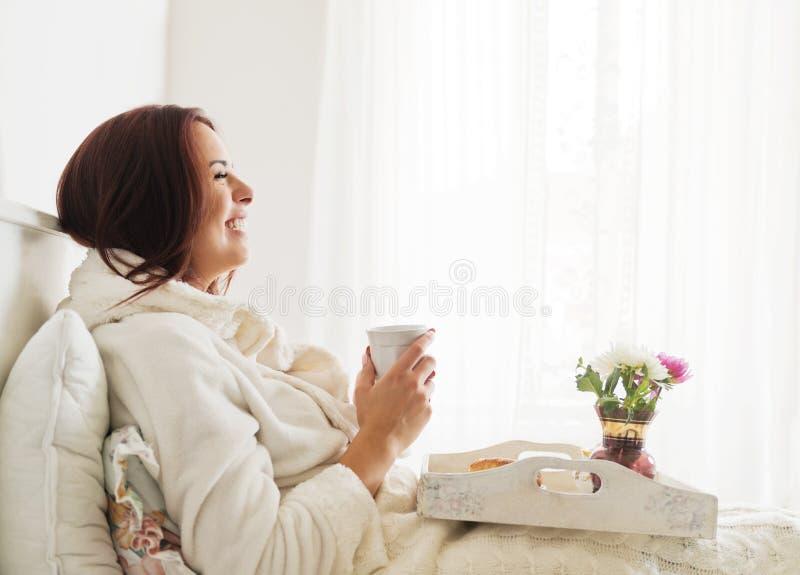 Όμορφη γυναίκα που βάζει και που απολαμβάνει το πρόγευμα στο κρεβάτι στοκ φωτογραφίες