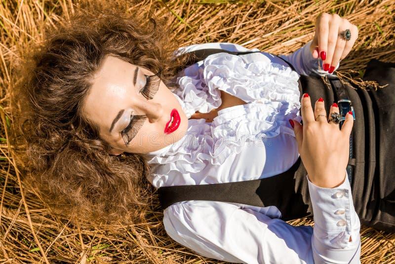 Όμορφη γυναίκα που βρίσκεται στη χλόη με τις προσοχές ιδιαίτερες στοκ εικόνες