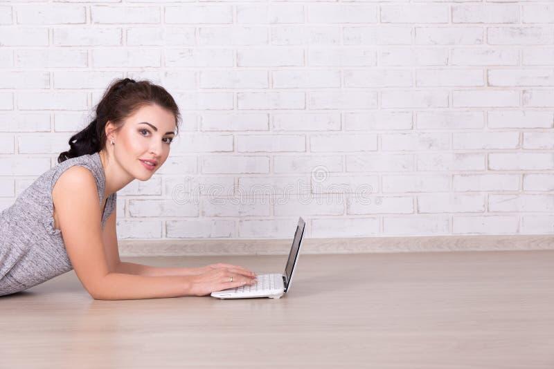 Όμορφη γυναίκα που βρίσκεται στο πάτωμα και που χρησιμοποιεί το lap-top στο σπίτι και στοκ εικόνα