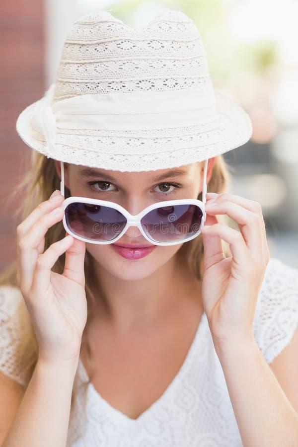 Όμορφη γυναίκα που γέρνει τα γυαλιά ηλίου της στοκ εικόνες