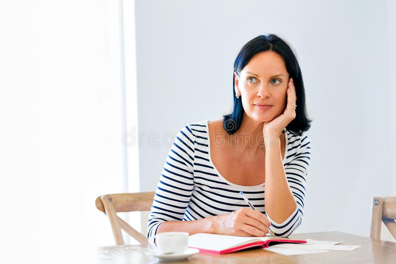 Όμορφη γυναίκα που γράφει σε μια ημερήσια διάταξη στο σπίτι ή το γραφείο στοκ εικόνα με δικαίωμα ελεύθερης χρήσης
