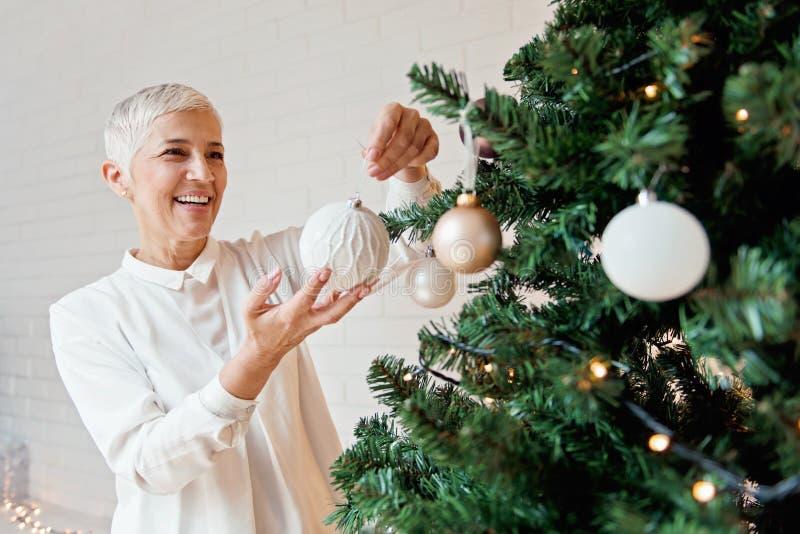 Όμορφη γυναίκα που διακοσμεί ένα χριστουγεννιάτικο δέντρο στοκ εικόνες με δικαίωμα ελεύθερης χρήσης