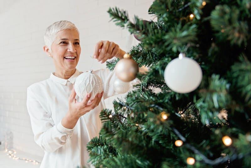 Όμορφη γυναίκα που διακοσμεί ένα χριστουγεννιάτικο δέντρο στοκ φωτογραφία