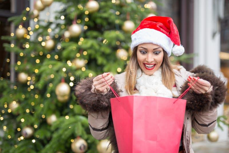 Όμορφη γυναίκα που εξετάζει μια τσάντα αγορών έκπληκτη στοκ εικόνα