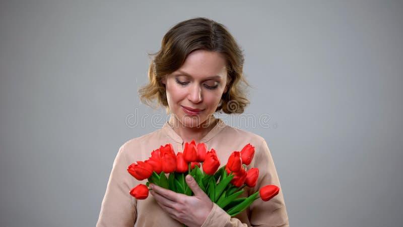 Όμορφη γυναίκα που εξετάζει τα λουλούδια από το θαυμαστή, ρομαντικό παρόν, επέτειος στοκ εικόνες