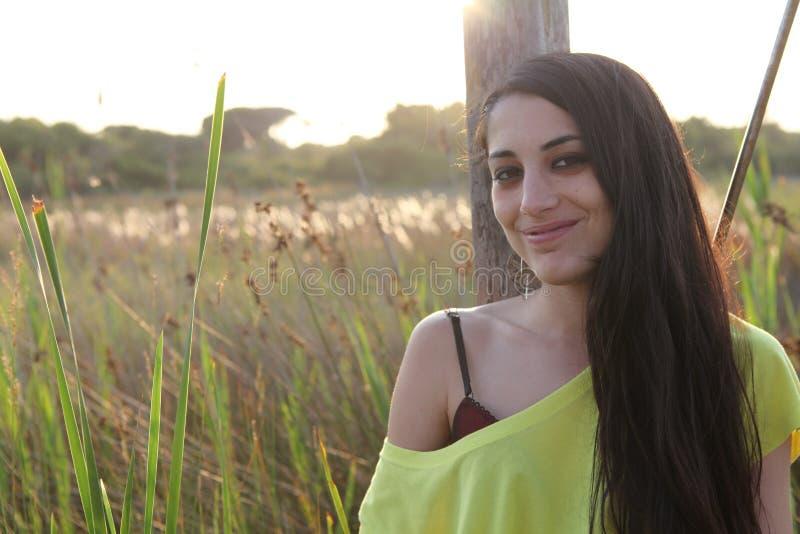 Όμορφη γυναίκα που εξετάζει τη κάμερα ευτυχής στοκ εικόνες
