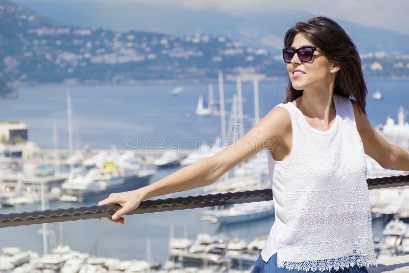 Όμορφη γυναίκα που εξετάζει το λιμάνι του Μόντε Κάρλο στο Μονακό Ακτή Azur στοκ εικόνες