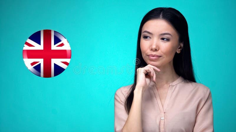 Όμορφη γυναίκα που εξετάζει το σημάδι σημαιών της Μεγάλης Βρετανίας, διεθνείς σχέσεις στοκ εικόνες με δικαίωμα ελεύθερης χρήσης