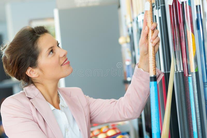Όμορφη γυναίκα που επιλέγει το ραβδί μπιλιάρδου στοκ εικόνες