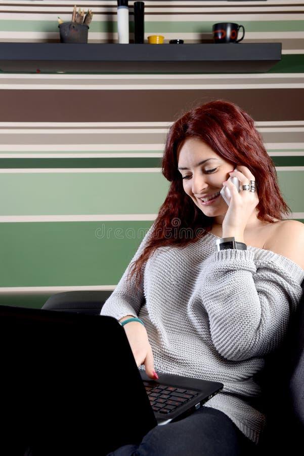 Όμορφη γυναίκα που εργάζεται στο lap-top στο σπίτι στοκ φωτογραφία