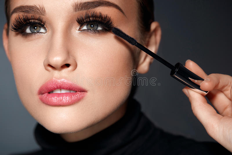 _ Όμορφη γυναίκα που εφαρμόζει μαύρο Mascara σε Eyelashes στοκ φωτογραφία