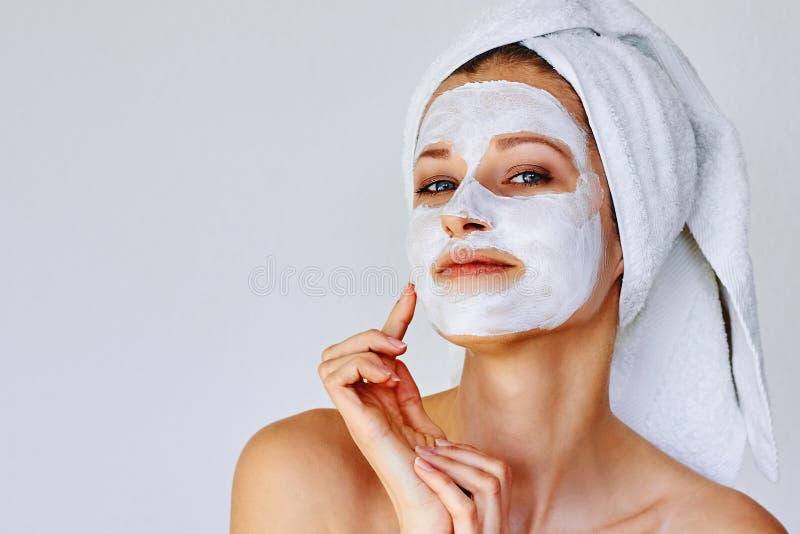 Όμορφη γυναίκα που εφαρμόζει την του προσώπου μάσκα στο πρόσωπό της Φροντίδα δέρματος και επεξεργασία, SPA, φυσικές ομορφιά και c στοκ φωτογραφία
