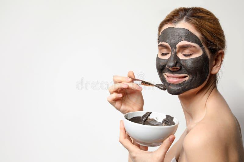Όμορφη γυναίκα που εφαρμόζει τη μαύρη μάσκα επάνω στο πρόσωπο στο ελαφρύ κλίμα στοκ φωτογραφίες με δικαίωμα ελεύθερης χρήσης