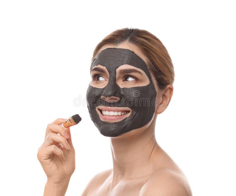 Όμορφη γυναίκα που εφαρμόζει τη μαύρη μάσκα επάνω στο πρόσωπο ενάντια στο λευκό στοκ φωτογραφίες με δικαίωμα ελεύθερης χρήσης