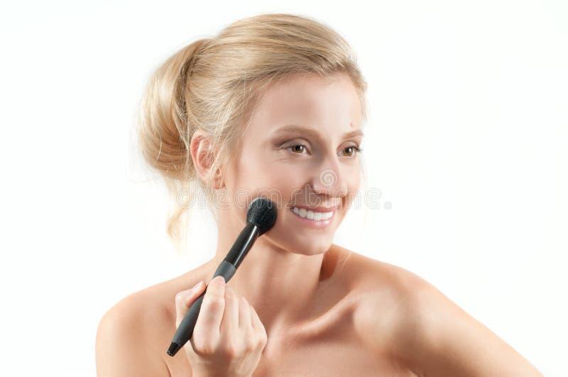 Όμορφη γυναίκα που εφαρμόζει το ξηρό καλλυντικό στο πρόσωπο που χρησιμοποιεί makeup τη βούρτσα στοκ εικόνα