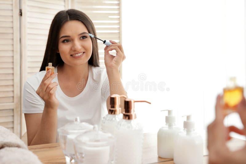Όμορφη γυναίκα που εφαρμόζει το πετρέλαιο επάνω στα eyelashes της κοντά στον καθρέφτη στοκ φωτογραφία
