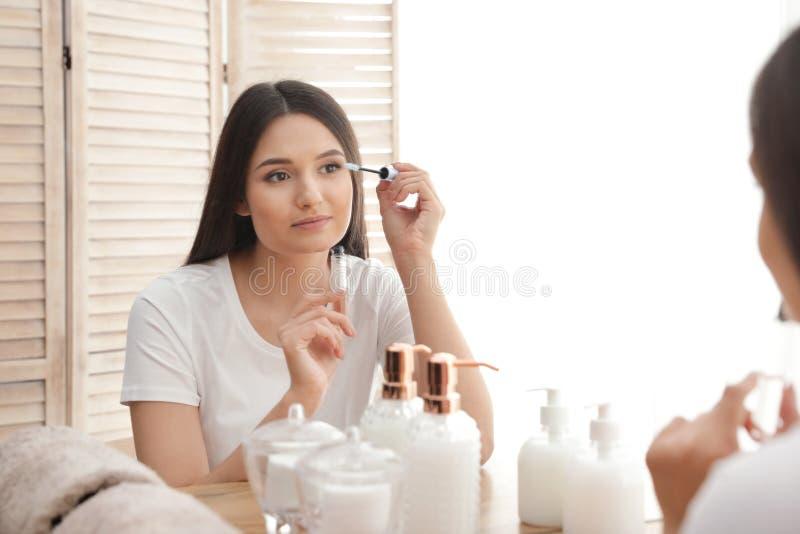 Όμορφη γυναίκα που εφαρμόζει το πετρέλαιο επάνω στα eyelashes της κοντά στον καθρέφτη στοκ εικόνες με δικαίωμα ελεύθερης χρήσης