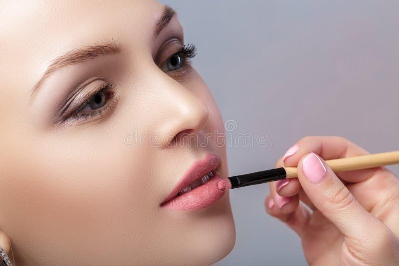 Όμορφη γυναίκα που εφαρμόζει το ρόδινο κραγιόν που χρησιμοποιεί τη βούρτσα για το makeup στοκ εικόνα με δικαίωμα ελεύθερης χρήσης