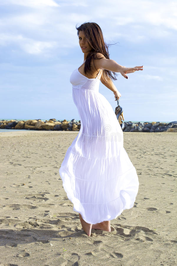 Όμορφη γυναίκα που θέτει και που χορεύει στην άμμο στοκ φωτογραφία με δικαίωμα ελεύθερης χρήσης