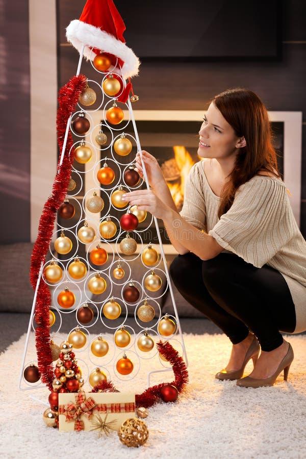 Όμορφη γυναίκα που διακοσμεί το σύγχρονο χριστουγεννιάτικο δέντρο στοκ εικόνες με δικαίωμα ελεύθερης χρήσης