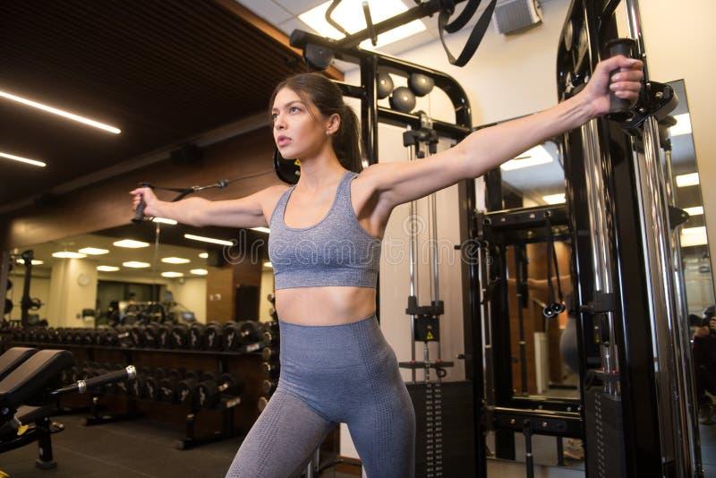 Όμορφη γυναίκα που κάνει γυμναστική στο γυμναστήριο φορώντας αθλητικά ρούχα στοκ εικόνες