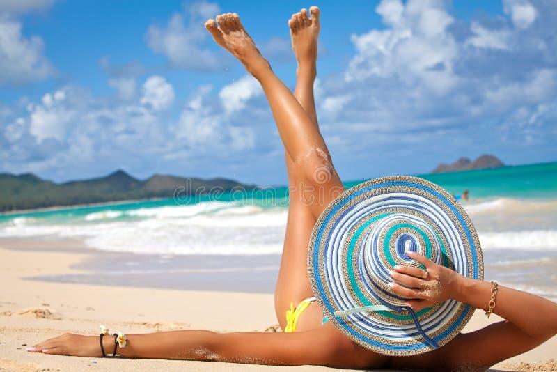 Όμορφη γυναίκα που κάνει ηλιοθεραπεία σε μια παραλία στοκ φωτογραφία