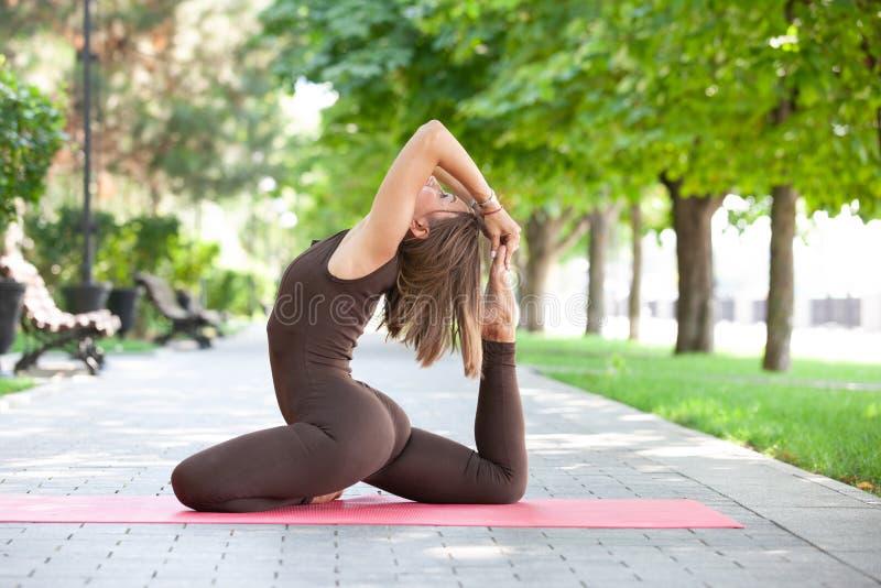 Όμορφη γυναίκα που κάνει τις ασκήσεις γιόγκας στο πάρκο στοκ εικόνες