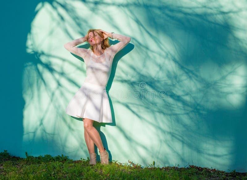 Όμορφη γυναίκα που κλίνει ενάντια στον μπλε τοίχο στοκ φωτογραφία
