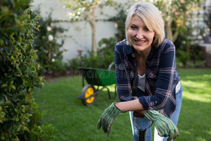 Όμορφη γυναίκα που κλίνει στον εξοπλισμό κηπουρικής στοκ εικόνες με δικαίωμα ελεύθερης χρήσης