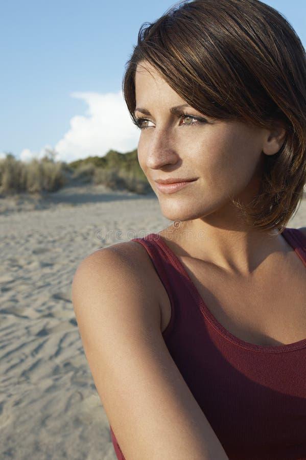 Όμορφη γυναίκα που κοιτάζει μακριά στην παραλία στοκ εικόνες